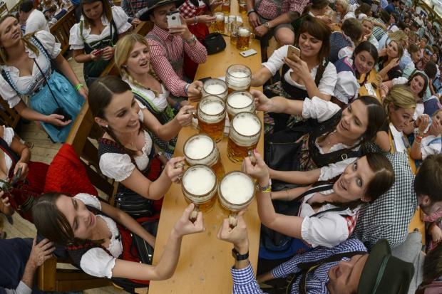 Revellers raise their steins of beer for a toast at the Hofbraeu tent on the opening day of the 2015 Oktoberfest in ...