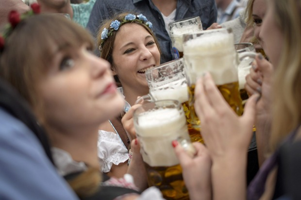 Revellers enjoy free beer at the Hofbraeu tent on the opening day of the 2015 Oktoberfest in Munich, Germany. The 182nd ...