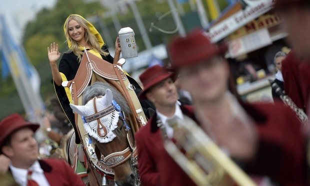 Laila Noeth, the Muenchner Kindl, waves while sitting on a horse during the landlord's parade on the opening day of the ...