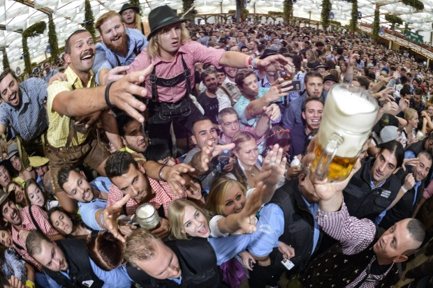 Revellers try to snatch free beer at the Hofbraeu tent on the opening day of the 2015 Oktoberfest in Munich, Germany. ...