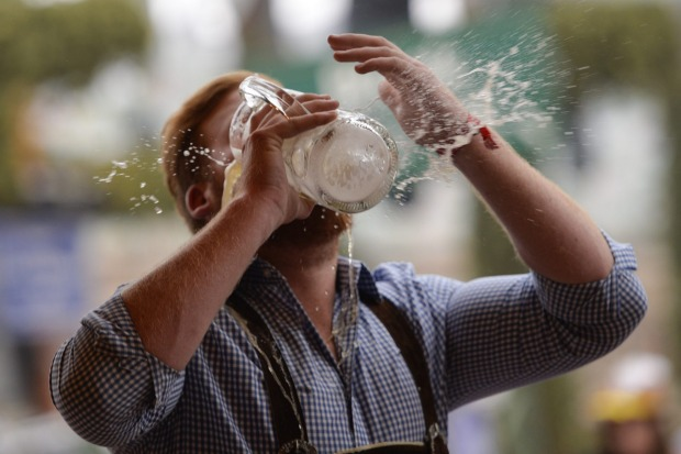A reveller spills beer as he tries to empty his stein in one sitting at the Hofbraeu tent on the opening day of the 2015 ...