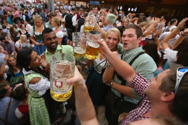 Revelers long for the first tapped beer mug at the Schottenhamel beer tent on the opening day of the 2015 Oktoberfest in ...