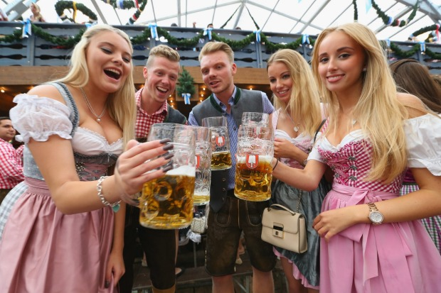 Revelers raise their beer glasses at the Schottenhamel beer tent on the opening day of the 2015 Oktoberfest in Munich, ...