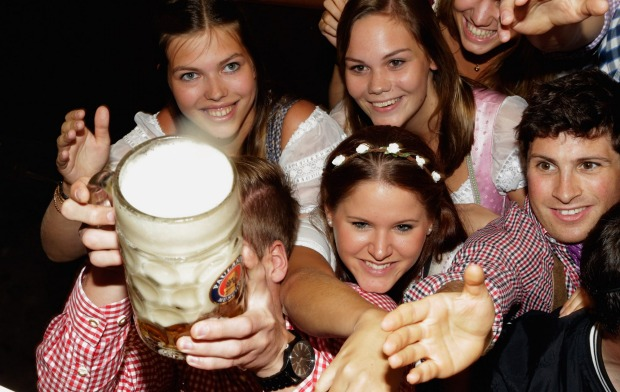 Revelers long for the first tapped beer mug at the Paulaner beer tent on the opening day of the 2015 Oktoberfest in ...