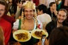 A reveller dressed as girl in mock Bavarian folk outfits makes fun during the opening day of the 2015 Oktoberfest in ...