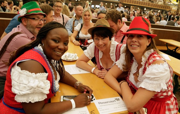 Revelers dressed in mock Bavarian folk outfits wait for the beer at Paulaner beer tent in Munich, Germany.