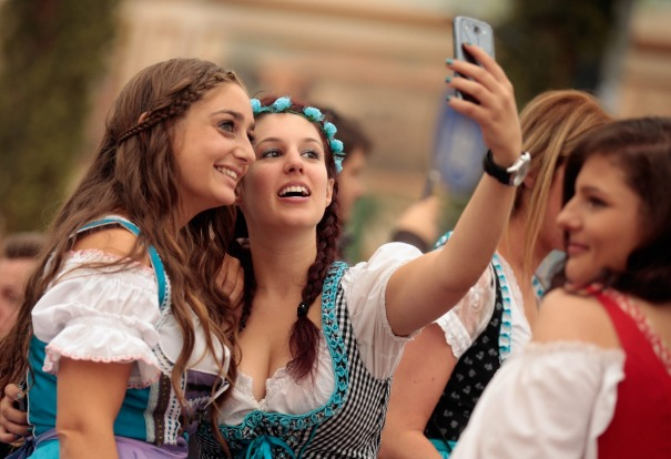Revelers dressed in Bavarian folk outfits pose for selfies during the opening day of the 2015 Oktoberfest in Munich, ...