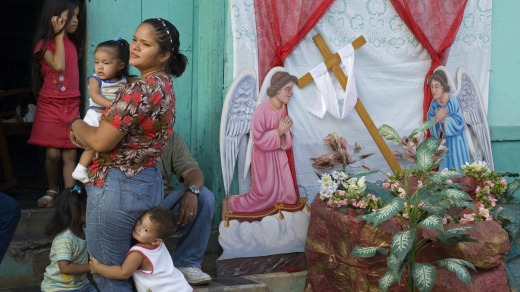 A family watches a  procession during Semana Santa.