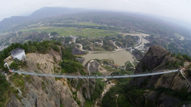 Tourists walk on the suspension bridge made of glass at the Shiniuzhai National Geological Park.