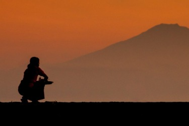 A Balinese woman makes an offering to Mt Batur early in the morning.