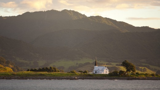The historic Anglican Christ Church cuts a lonely figure on its promontory in Papatea Bay.