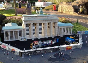 Tiny figures clamber atop a model of the Berlin Wall, built in front of a replica Brandenburg Gate.