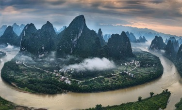 The Li River winds it's way though the hundreds of karst mountain peaks in Guilin, China and the Xianggong Mountain ...