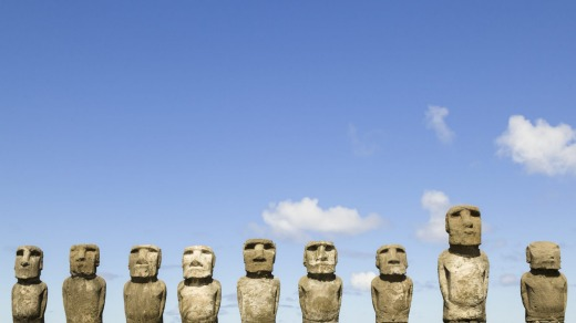 Moai statues line a stone platform at the heritage listed site of Ahu Tongariki, Easter Island.