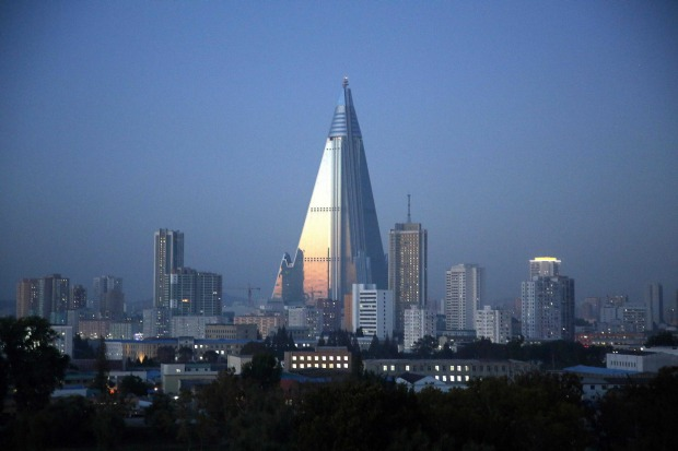 Dusk settles over Pyongyang, North Korea, as the 105-story pyramid-shaped Ryugyong Hotel towers over residential ...