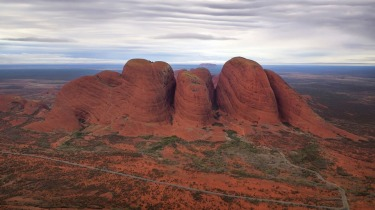 The view of Kata Tjuta in the early morning light with Uluru on the distant horizon all framed by low ethereal clouds combined to make a helicopter flight over the Red Centre an experience to remember.