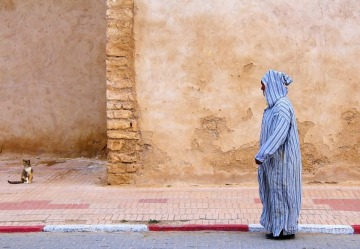 A Moroccan male dressed in the traditional pointy-hooded robe called the Djellaba (pronounced 'jallaba') on a morning ...