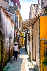 As we walked through the streets of Hoi An in Vietnam I looked up the lane and saw this woman walking up the lane in the ...