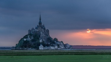 Mont Saint-Michel, in Normandy, France, at sunrise. The closest you can get by car is the car park at the visitors' ...