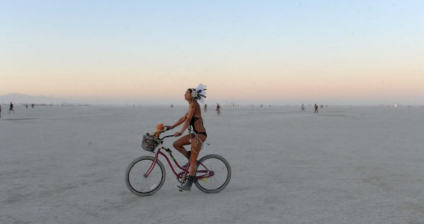 A woman rides a bicycle on the playa after sunset at the Burning Man festival in Gerlach, Nevada. Once a year, tens of ...