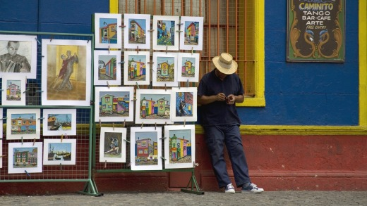 An artist stands alongside his work for sale, in the popular tourist area of La Boca.