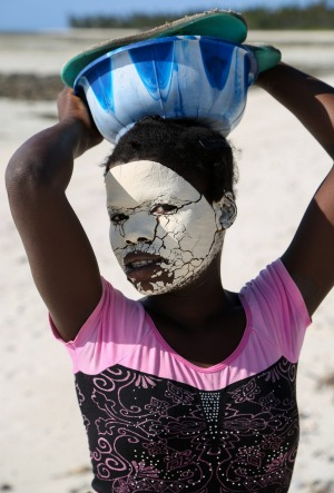 A young woman on Matemo Island's beach. Local women wear natural make-up to protect their skin from the sun.
