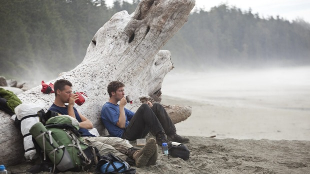 Hikers sit against a giant driftwood log sipping hot tea.
