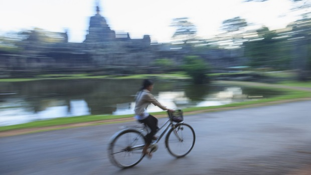 A local woman on her way past Angkor Wat.