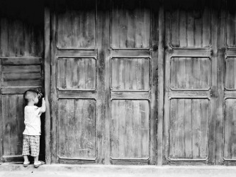 Hoping to escape the relative commercialism of Yangshuo, I ventured to the nearby ancient town of Xingping in Guangxi Province. Whilst wandering the old, cobbled streets, I came across this cute scene of a little boy playing a game of hide and seek, virtually dwarfed by the huge wooden doors.