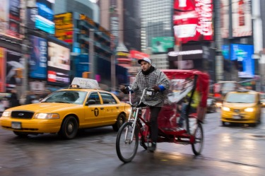 Working hard, a rider taxis some people through Times Square in New York in the rain.