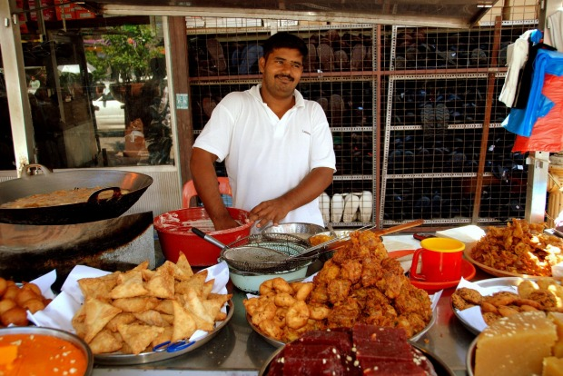 GEORGETOWN, MALAYSIA: Street vendor offers a dazzling variety of delicious Indian foods on Lebuh Penang in Little India.
