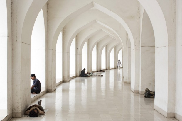 Bangladeshi Muslims sit at the Baitulmukarram Mosque in Dhaka, Bangladesh.