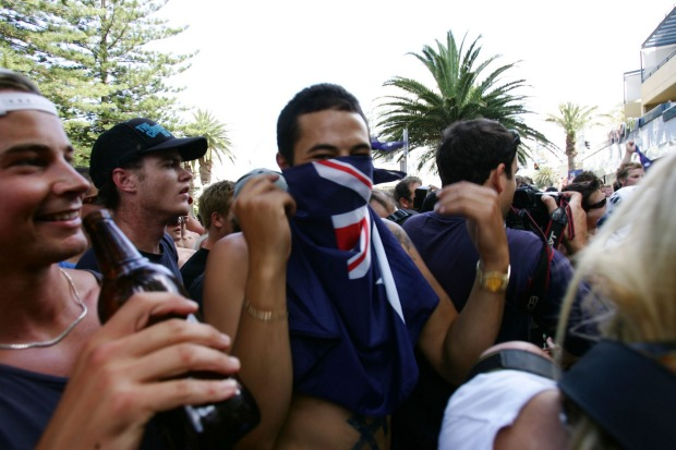 A man hides his face with the Australian flag on the day of violence in Cronulla.