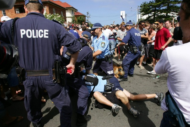 Police officers pile on top of a man after he attempted to escape custody during the riots.