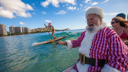Santa arrives by outrigger canoe at the Outrigger Waikiki Beach Resort in Hawaii.
