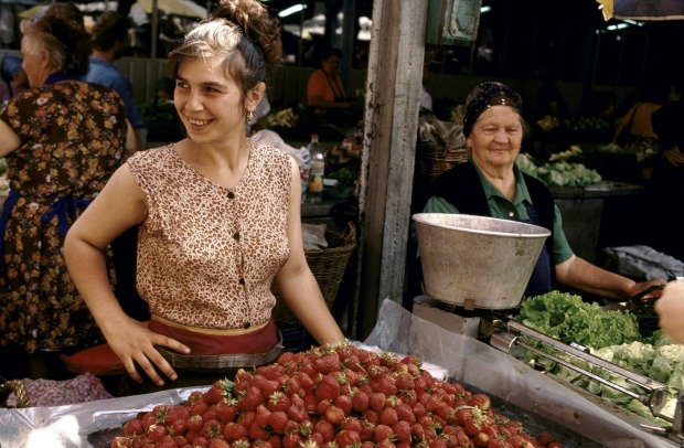 Young woman sells strawberries at a market stall.