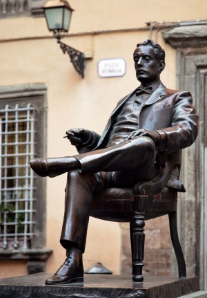 Giacomo Puccini is depicted in his birthplace, Lucca, holding his omnipresent cigar.