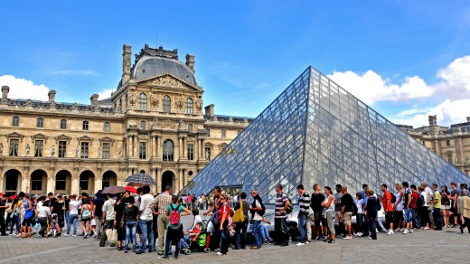 Tourists queue before the Pyramid of Louvre museum, Paris, France.