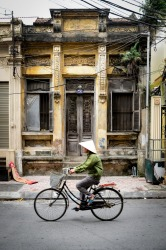 A local passing through a typical scene in Ha Noi, Vietnam, with decaying French colonial buildings and chaotic power lines.