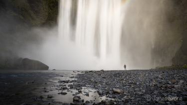 A lone figure poses at the base of Skógafoss, the highest waterfall in Iceland.