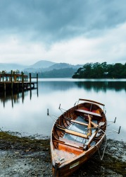 Boats await the tourist rush that will eventuate later in the day on the shores of Derwentwater Lake , Keswick , in the ...