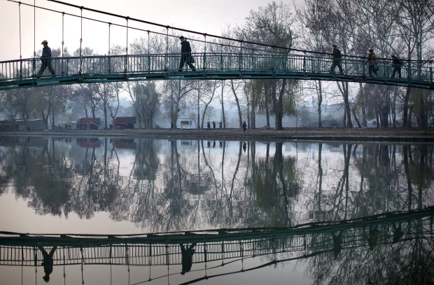 North Koreans walk on a bridge that takes them over the Pothong River in Pyongyang, North Korea. The Pothong River is ...