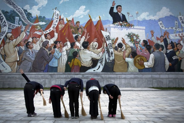 North Korean school girls holding brooms bow to pay their respects toward a mural which shows the late North Korean ...