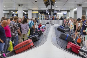 Travelers wait for their luggage from a conveyor belt.