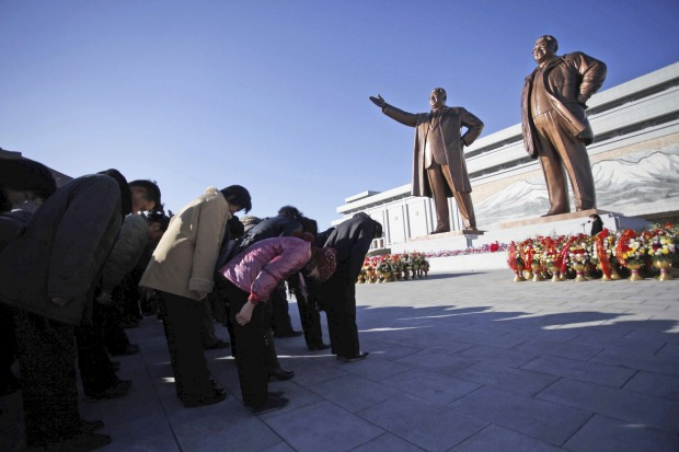 North Koreans bow on Mansu Hill, where bronze statues of late leaders Kim Jong Il and his father, Kim Il Sung, in ...