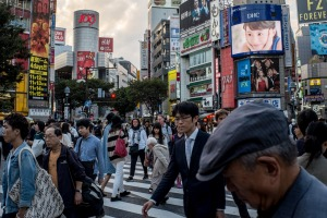 Pedestrians cross the road at Japan's famous Shibuya crossing.