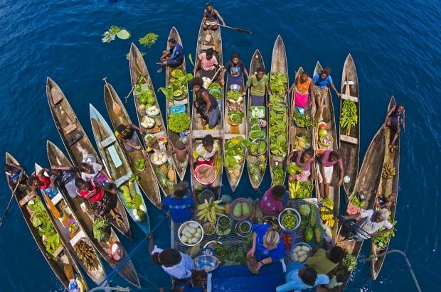 A boat market visits a cruise ship in the Solomon Islands.