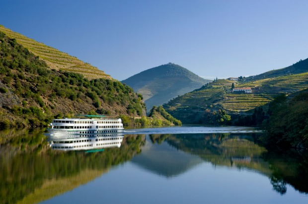 A boat cruises the Douro river between Regua and Pinhao, the Alto Douro district, Portugal.