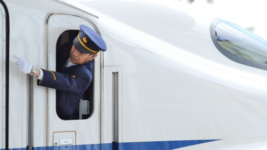 Precision: A guard giving hand signals on a bullet train.