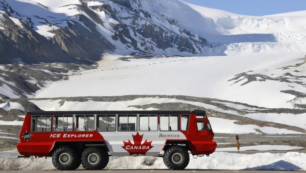 Parking snowcoach in front of the Athabasca Glacier, Canada.